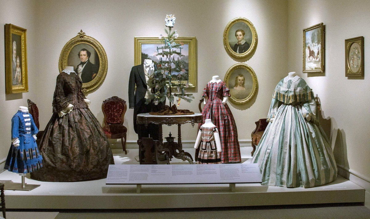 From left, boy's suit, unknown maker, circa 1860; rust brown and black dress, unknown maker, circa 1853; man's suit courtesy of The Costumer, Schenectady, N.Y.; girl's red and green plaid dress, unknown maker, 1855–65; child's plaid dress, unknown maker, 1840–50; and green and white striped dress, unknown maker, 1853–57, silk with fringe. The table is by Hertz and Lehmann, Albany, N.Y., circa 1862.