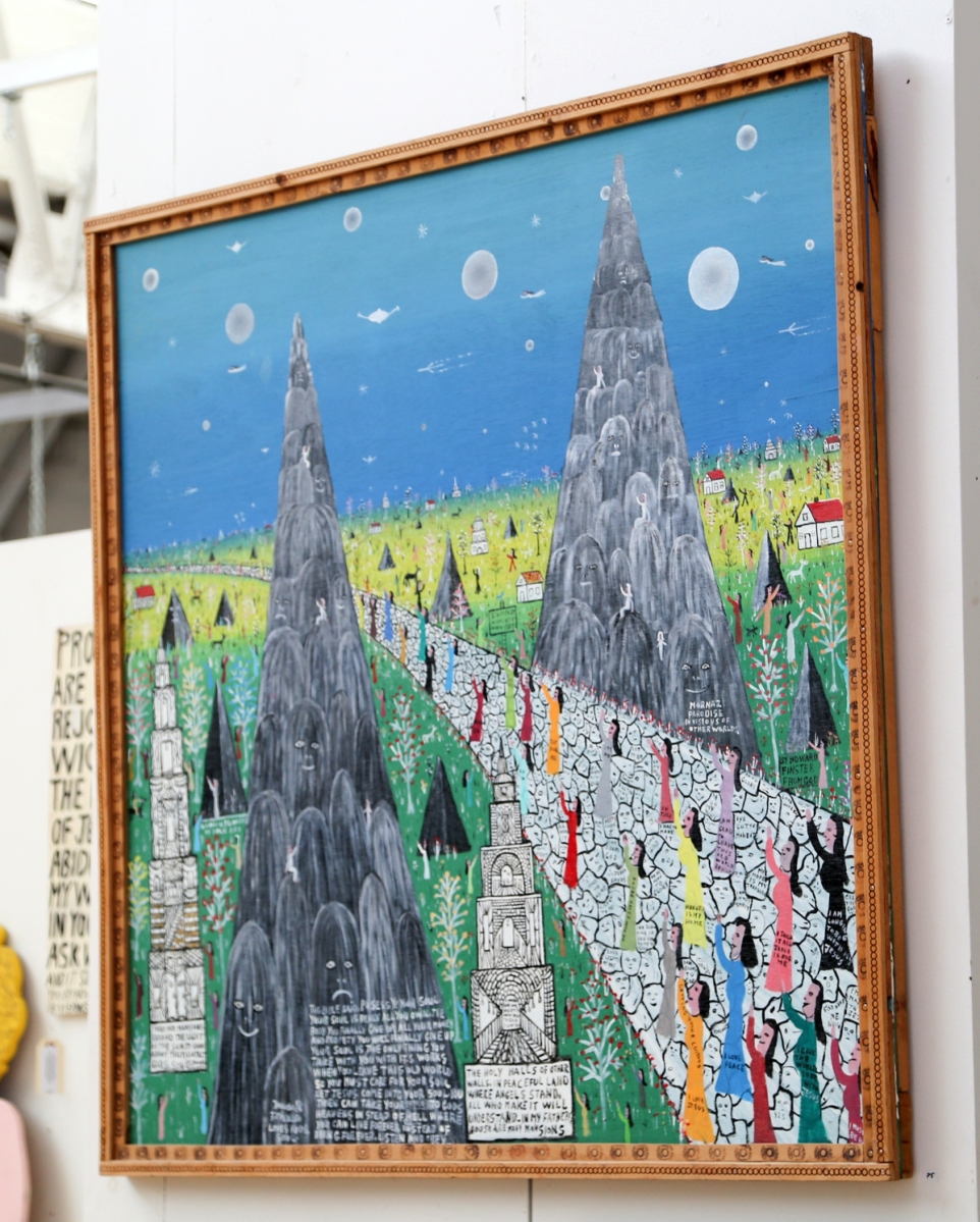"""The top lot of the art sale was this 48-by-48-inch painting on wood painting by Howard Finster. """"Visionary Landscape, #4494"""" caught $31,250, between the estimates. It was a highly detailed work from the artist in a large-scale format, featuring worshipers and angels walking along a stone-paved road between two sharply rising mountains. The frame was made by Finster as well."""