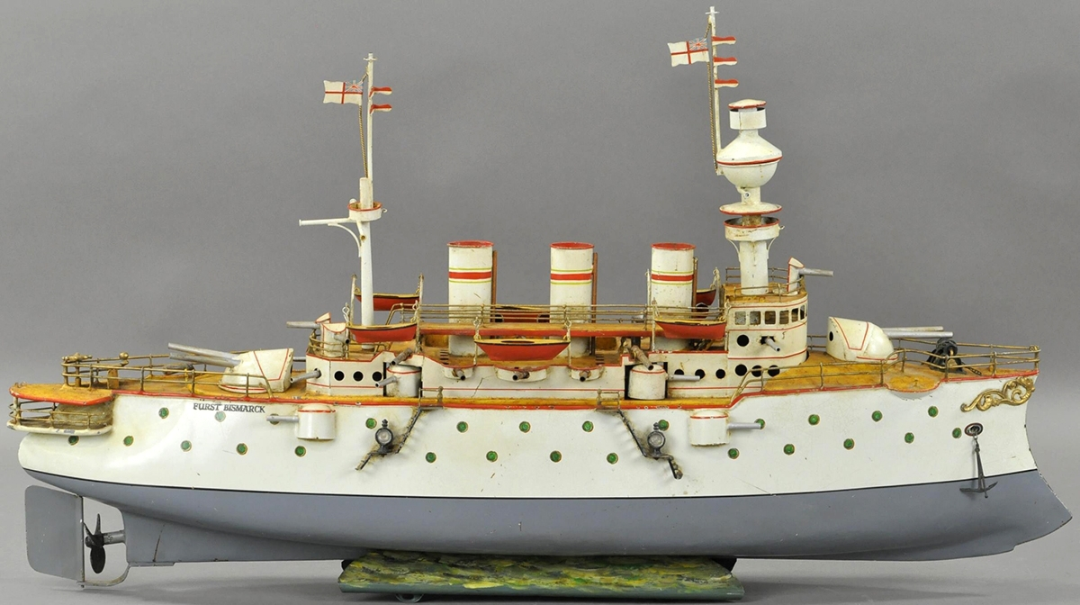 This Bing Furst Bismark Battleship, with three stacks and green portholes, elaborate cast metal decorations on its bow, 32 inches long, sold for $18,000, within estimate. It has been professionally restored and features multiple large cannons and several smaller guns and two detailed masts with British flags and crow's nest.