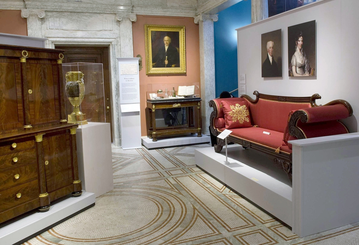 A view of an exhibition gallery devoted to furniture, left, made for David Sears; center, for John Davis Williams (1770–1848); and right Stephen (1746–1829) and Elizabeth Salisbury (1768–1851). The linen press, left, is attributed to Isaac Vose & Son, 1819–22, and is from a private collection. The portrait of Williams, center, is attributed to Chester Harding, 1830–40 and is owned by the South End Historical Society. It hangs above a pier table, one of a pair attributed to Vose, Coates & Company that belonged to Williams. Right, the portraits of Stephen and Elizabeth Salisbury are by Gilbert Stuart, 1823–24. The sofa is attributed to Isaac Vose & Son, with Thomas Wightman, carver, Boston, circa 1820.