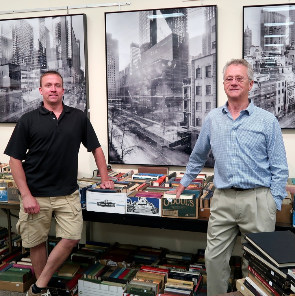 """Eddie and Ed Nadeau with three of four large, framed c-prints by German art photographer Michael Wesely (b 1963) depicting the Museum of Modern Art. The images are inscribed """"Michael Wesely 9.8.2001-7.6.2004 The Museum of Modern Art for David and Peggy Rockefeller"""". The four c-prints brought $12,535."""