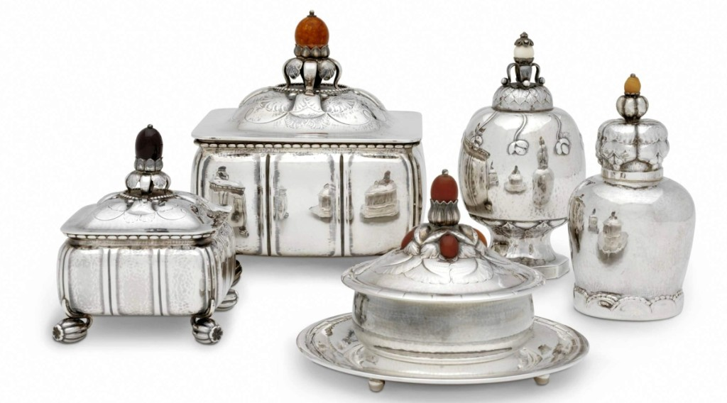 These examples of silver hollowware with nature-based ornament and lightly hammered surfaces illustrate Georg Jensen's own roots in the Arts and Crafts style. Box, tobacco caddy, butter dish and tea caddies, models 30, 30C, 44, 46 and 137, by Georg Jensen, designed 1912–14. Lent from a personal collection.