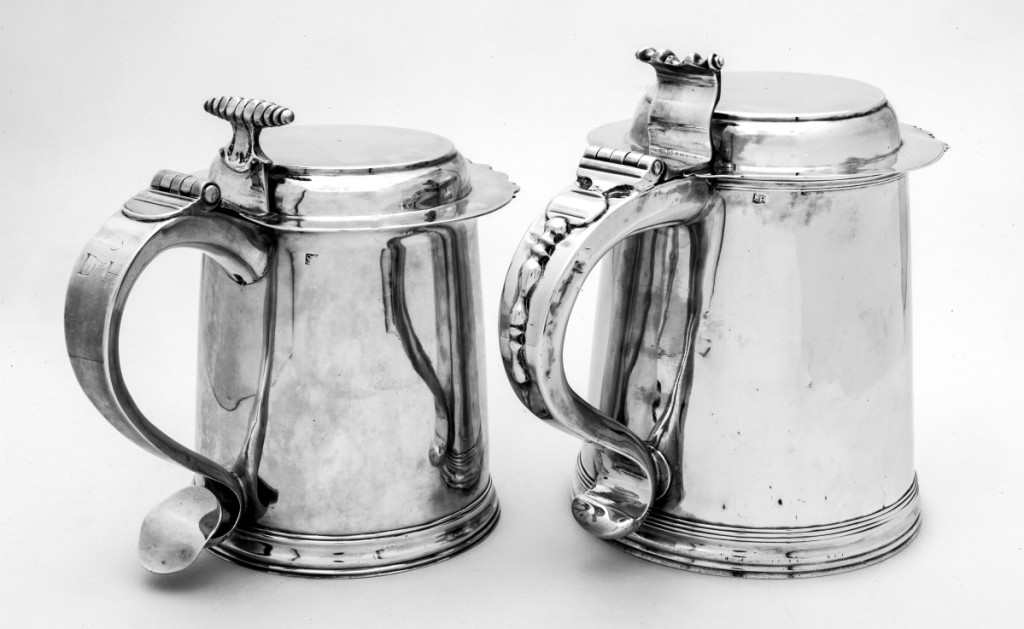 """Left, flattop tankard marked by Simeon Soumaine (baptized 1685–circa 1750), New York City, 1730–1750. Engraved on handle with block initials """"S/D*H,"""" for Daniel 2d (1690/1–1763) and Hannah Brewster Smith (169 –1761); engraved on base in later script """"David & Hannah Smith/Smithtown, Long Island/1691–1763."""" Silver; height 6-  inches. Preservation Long Island, gift of Miss Alice Lawrence. Right, flattop tankard marked by Elias Pelletreau, 1750–1776. Engraved with block initials """"I/I*M"""" on base. Silver; height 7½ inches. Preservation Long Island, gift of Howard C. Sherwood, 957.608. Photo Glenn Castellano. The Soumaine tankard came down in the family of General John Smith (1752–1816), a US Representative and Senator, the grandson of Daniel 2d and Hannah Brewster Smith, to the donor."""