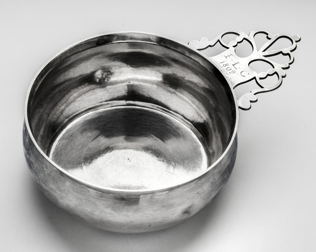 """Porringer with keyhole handle, marked by shop of Elias Pelletreau with stamp Mark 4; made by John Pelletreau (1755–1822), 1802. Engraved on handle obverse in block letters """"JLG/1802"""" for John Lyon Gardiner (1770–1816). Silver; height 2 inches, length 7½ inches. Courtesy of Suffolk County Parks, Division of Historic Services. Photo Glenn Castellano."""