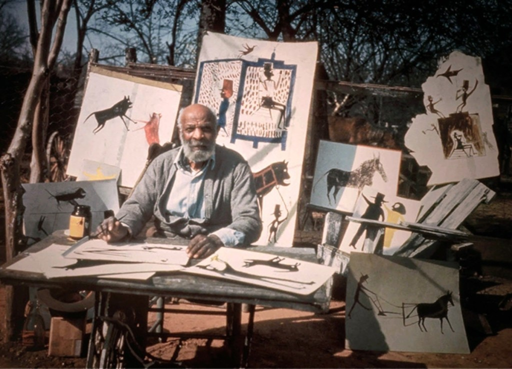 Bill Traylor sits before a display of his artwork. Photograph by Horace Perry. Courtesy Alabama State Council on the Arts.