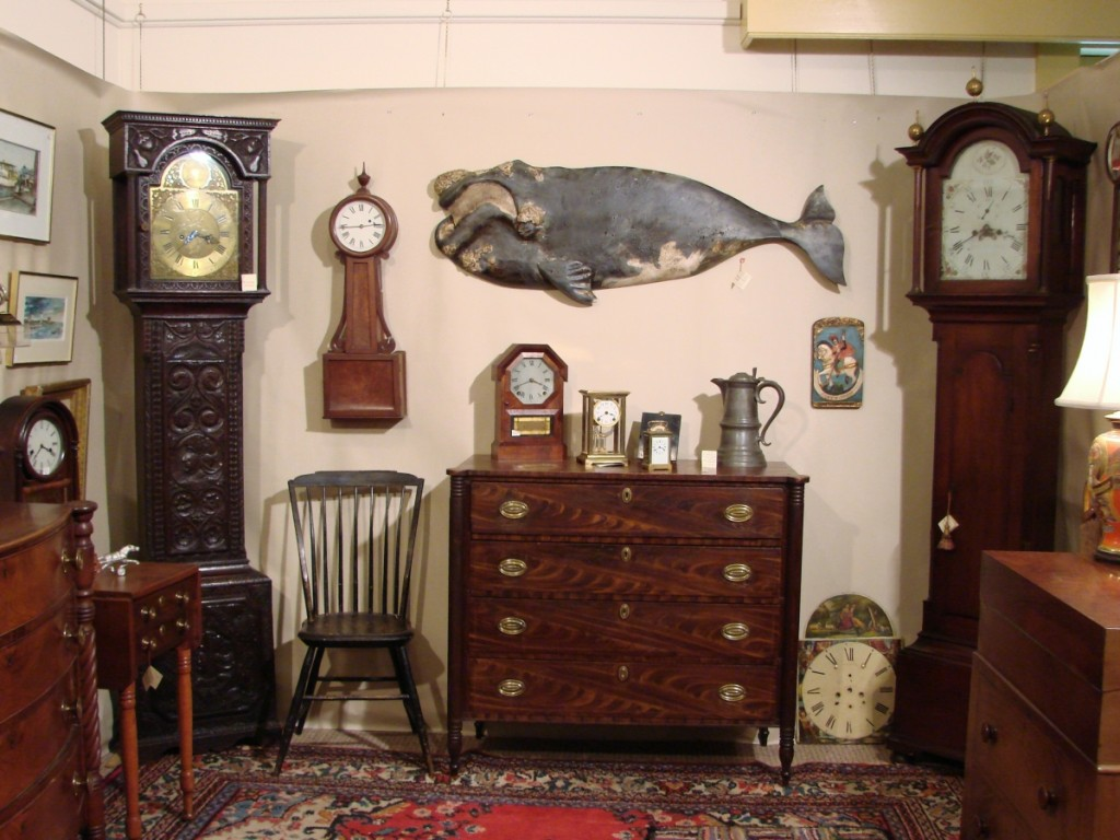"The heavily carved circa 1780 tall case clock in the corner of the booth of Harrison, Maine, dealer Harry Hepburn III was made by Joseph Atkinson in Ireland. The well-carved whale plaque by ""Wick"" Ahrens was priced at $8,775."