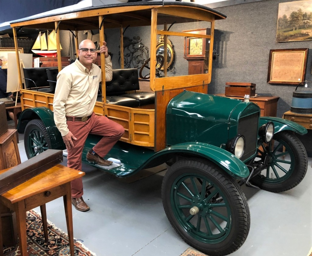 Firm president Kevin Bruneau with a 1922 Ford Model T wood body depot hack truck that sold for $9,600 ($8/$12,000). The automobile, recently restored, is in generally good condition and came from a Rhode Island collection.