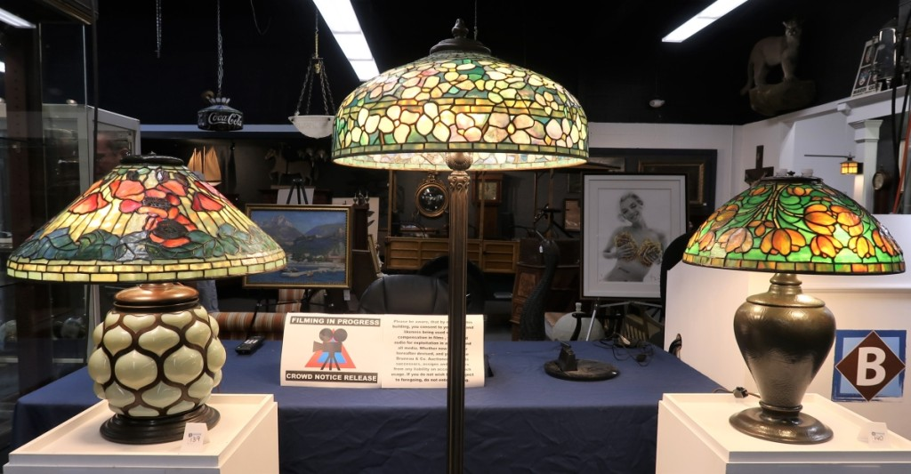 Three Tiffany Studios lamps from a Houston collection grossed $250,800. From left, a circa 1910 table lamp with a Poppy shade and a blown-glass and bronze base, $108,000 ($80/120,000); a circa 1910 bronze and glass floor lamp with a Dogwood shade, $114,000 ($90/120,000); and a circa 1915 table lamp with a Crocus shade on a bronze pine needle pattern base, $28,800 ($25/35,000).
