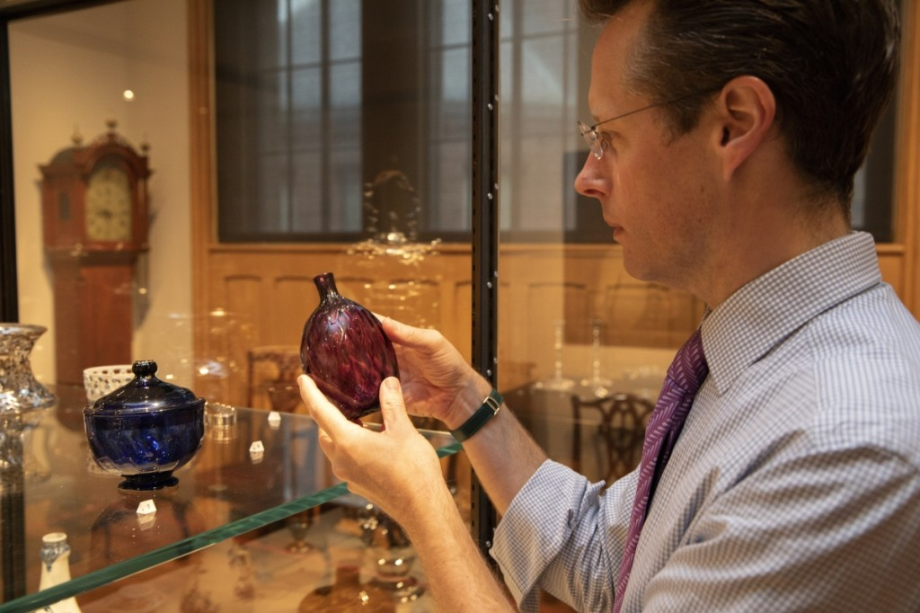 Curator John Stuart Gordon inspects a pocket bottle possibly made by Henry William Stiegel at the American Flint Glass Manufactory in Manheim, Penn., between 1764 and 1770.