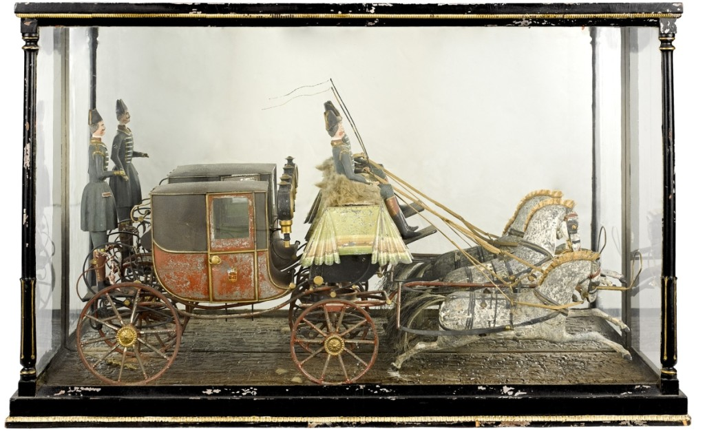 In a glass display case was an English painted tin and wood horse-drawn royal coach model, Nineteenth Century, with two wooden horses, driver and rear guard. It sold over the $1,600 high estimate for $4,148.