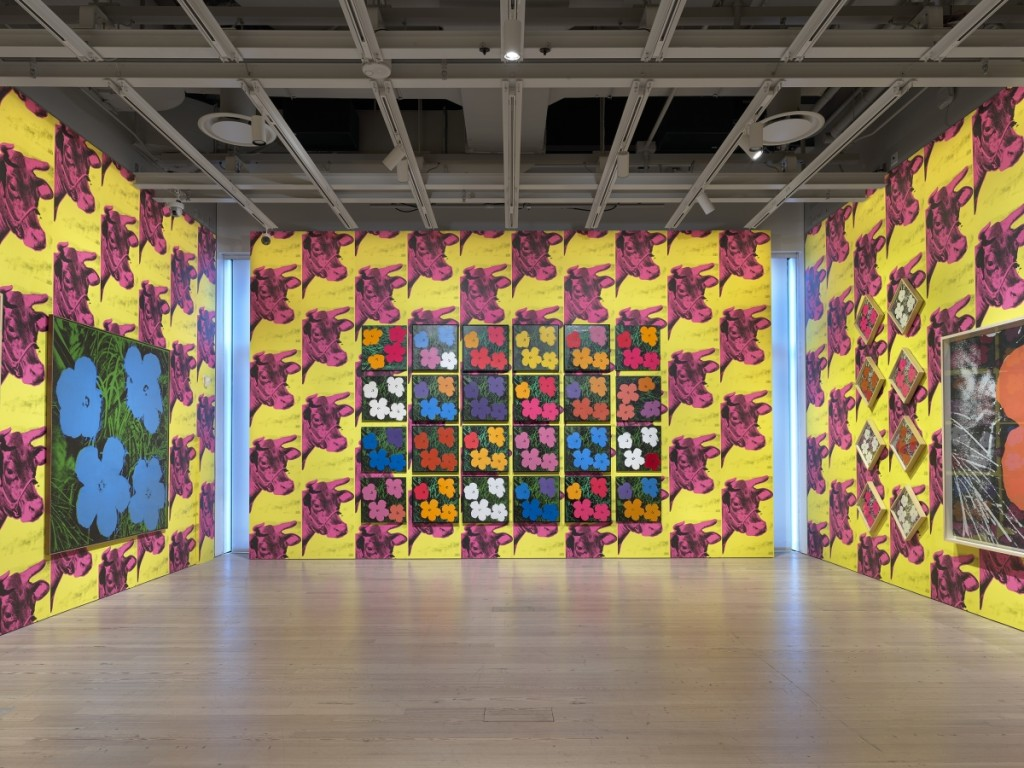 "Installation view of ""Andy Warhol – From A to B and Back Again"" at the Whitney Museum of American Art, New York. Back wall featuring 24 variations of ""Flowers,"" 1964; Left wall featuring ""Flowers [Large Flowers],"" 1964–65. Photograph by Ron Amstutz. ©2018 The Andy Warhol Foundation for the Visual Arts, Inc / Licensed by Artists Rights Society (ARS), New York."