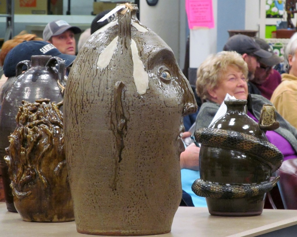 Clint Alderman's 10-gallon double handle face jug appears to be watching the action from a display table in the center of the bidder's seating area. He brought a respectable $900 when his turn came.