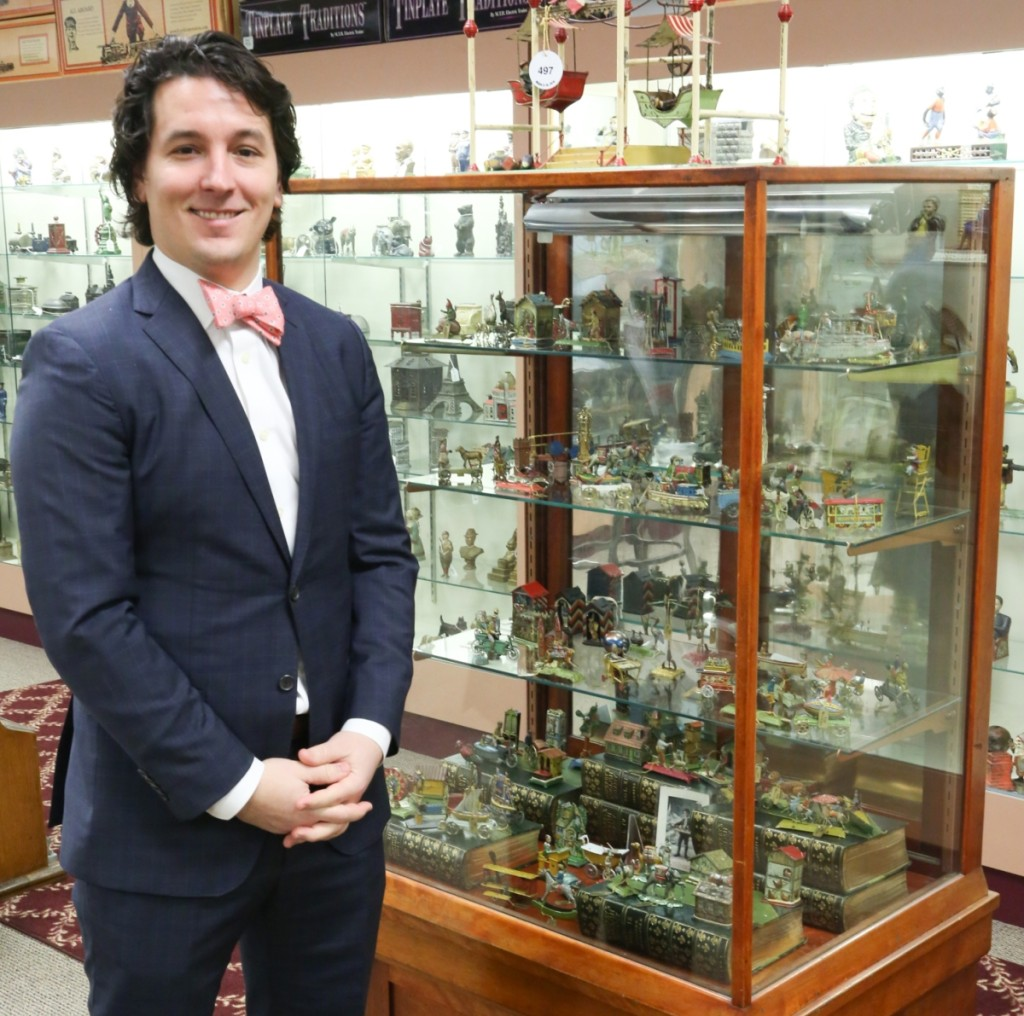 Michael Bertoia stands with his collection of penny toys. Bertoia began collecting them with his father, Bill Bertoia, when he was ten years old, and two decades later was willing to part with them in pursuit of other areas of collecting interest. He kept half of the remaining collection to pass down to his son, Aldo William Bertoia.