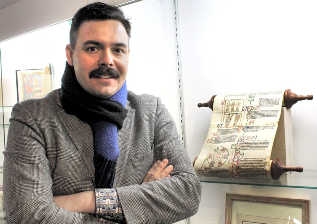 Les Enluminures vice president Keegan Goepfert stands next to a Thirteenth Century illustrated scroll summarizing biblical history from Adam to Christ. The last known example in private hands, it is 3 meters long when unfurled.