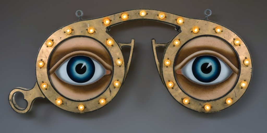 Optician's trade sign, E.G. Washburne & Co., 207 Fulton Street, New York City, circa 1915. Paint and gold leaf on zinc and iron, with glass and light bulbs; 26 by 54 by 4 inches. Collection of Penny and Allan Katz.                —Gavin Ashworth photo