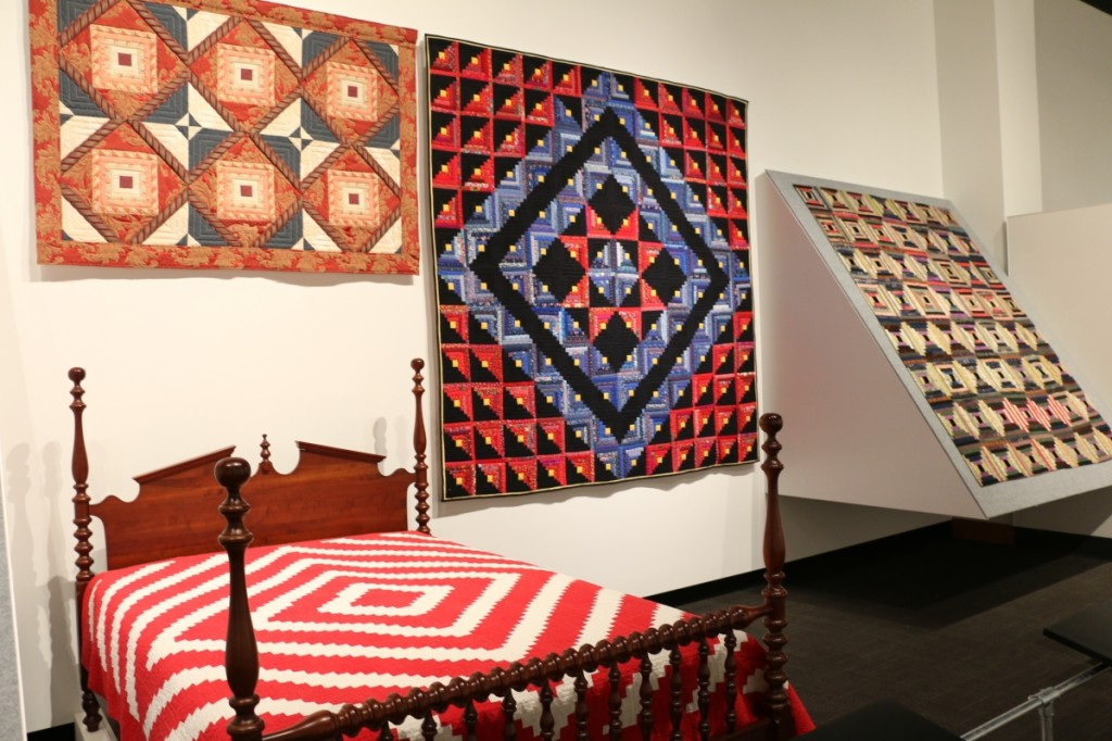 Two versions of a Log Cabin pattern quilt are displayed side by side. On the bed, a Barn Raising variation made in the 1920s in Rutherford County. Cotton with cotton batting; hand pieced. On the wall, a late-Twentieth Century Star variation by Charles Goddard (1927–2012) made in Memphis, Shelby County. Cotton with polyester batting; hand pieced.