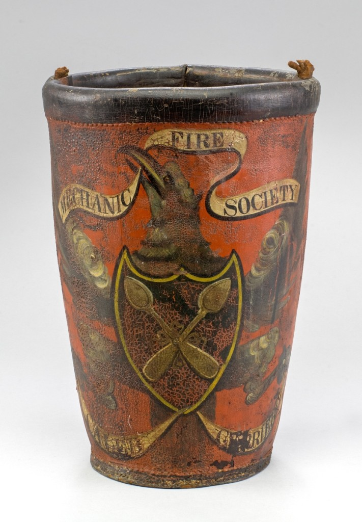 """Attributed to John S. Blunt (1798–1835), inscribed """"Firebucket owned by Caleb Currier,"""" Portsmouth, circa 1825. Painted leather; 12 inches high, 8¼ inches diameter. Portsmouth Historical Society; Gift of Mrs Alice Vaughn Johnson."""