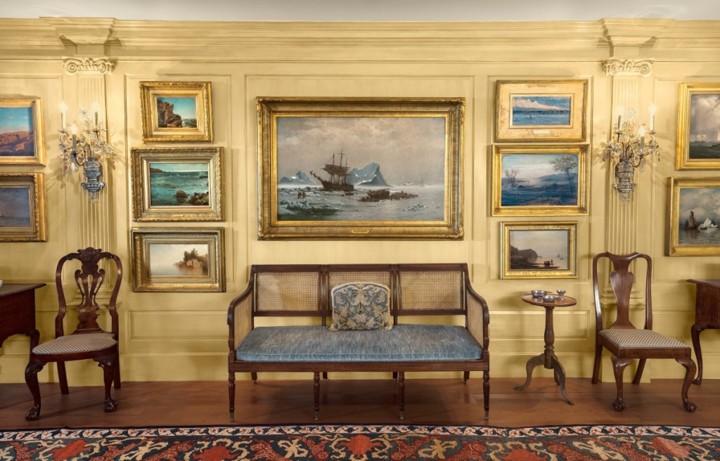 "The Lynches displayed maritime paintings and coastal views in the East Room of their Marblehead Neck house. A treasure of the collection is ""Among the Ice Floes,"" center, by William Bradford. The oil on canvas of 1878 hangs above a circa 1810 caned settee, possibly from the shop of Duncan Phyfe. It is flanked by groupings of Eighteenth Century furniture from Philadelphia and Boston. © Peabody Essex Museum. Photography by Kathy Tarantola."