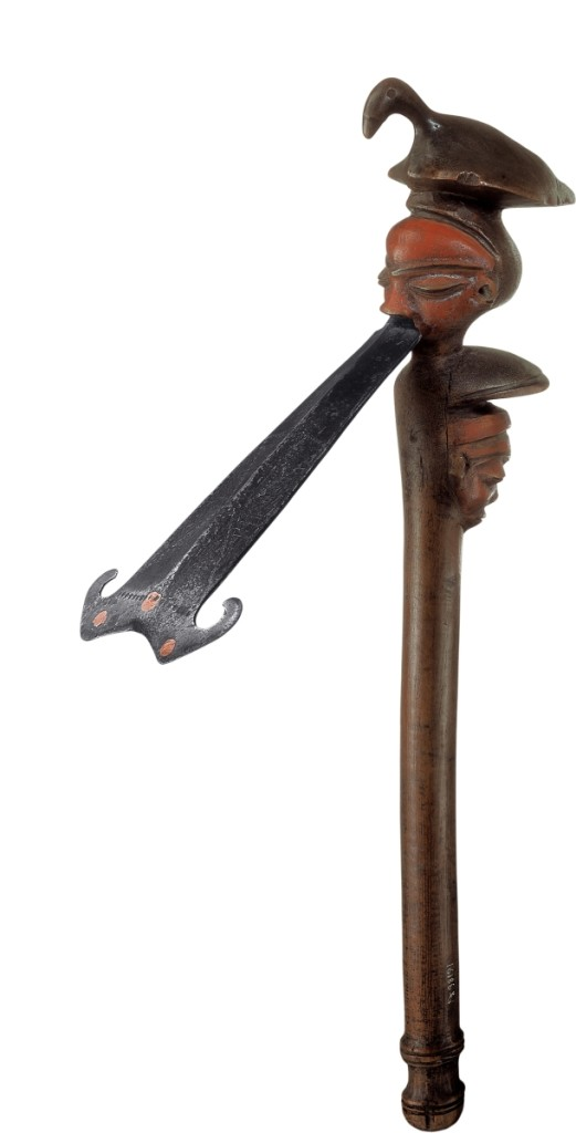 This ceremonial adze, with its tonguelike iron blade, once dignified the left shoulder of a Pende chief who wore it as an emblem of high office when traveling. Never intended to carve wood, the adze represented smooth-cutting diplomacy, straight talk, and efficient negotiation. The bird at the top alludes to the chief's bird's-eye view, or oversight, of his domain. In contrast, the calm, masklike face from which the blade emerges is protected by another set of eyes, keeping watch behind him. Adze by Central Pende artist, Democratic Republic of the Congo, early Twentieth Century. Iron, wood, copper, pigment. Felix Collection.