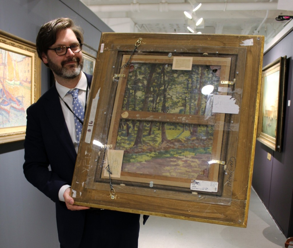 """Zachary Hall showing the reverse of Raoul Dufy's """"La Cite, Vue de L'Hotel de Ville,"""" to show that Dufy frequently reused canvases; it was one of a few works in the booth that had works on the reverse. Trinity House Paintings, New York City, London and The Costwalds."""