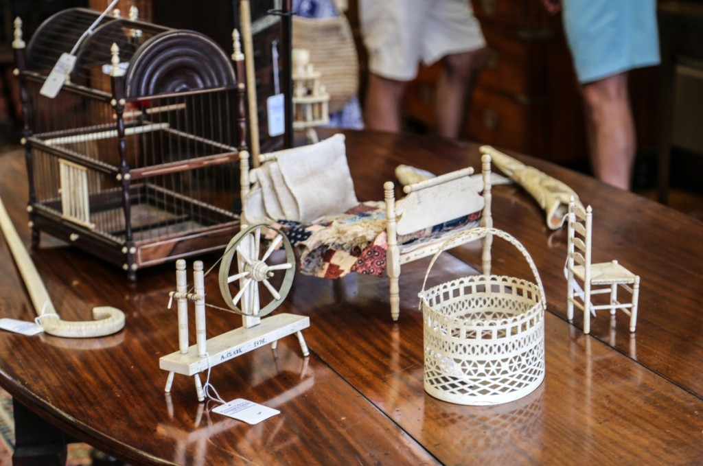 """Nearly $40,000 in miniature whalebone works can be seen here. At front is a whaleman-made Nantucket pierced swing handle scrimshaw basket that brought $15,860. The whalebone doll's bed behind followed closely at $14,640. The spinning wheel to the left was inscribed """"A. Clark 1876"""" and took $6,250. The little chair on the right, a whaleman-made whalebone ladderback rush seat side chair, brought $3,172."""