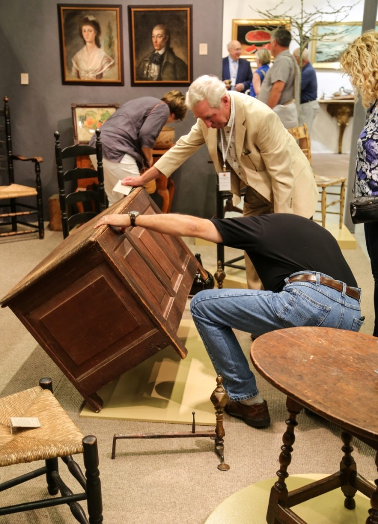 A buyer gets a closer look at Peter Eaton's Seventeenth Century pilgrim paneled chest in original red wash. It sold opening day.