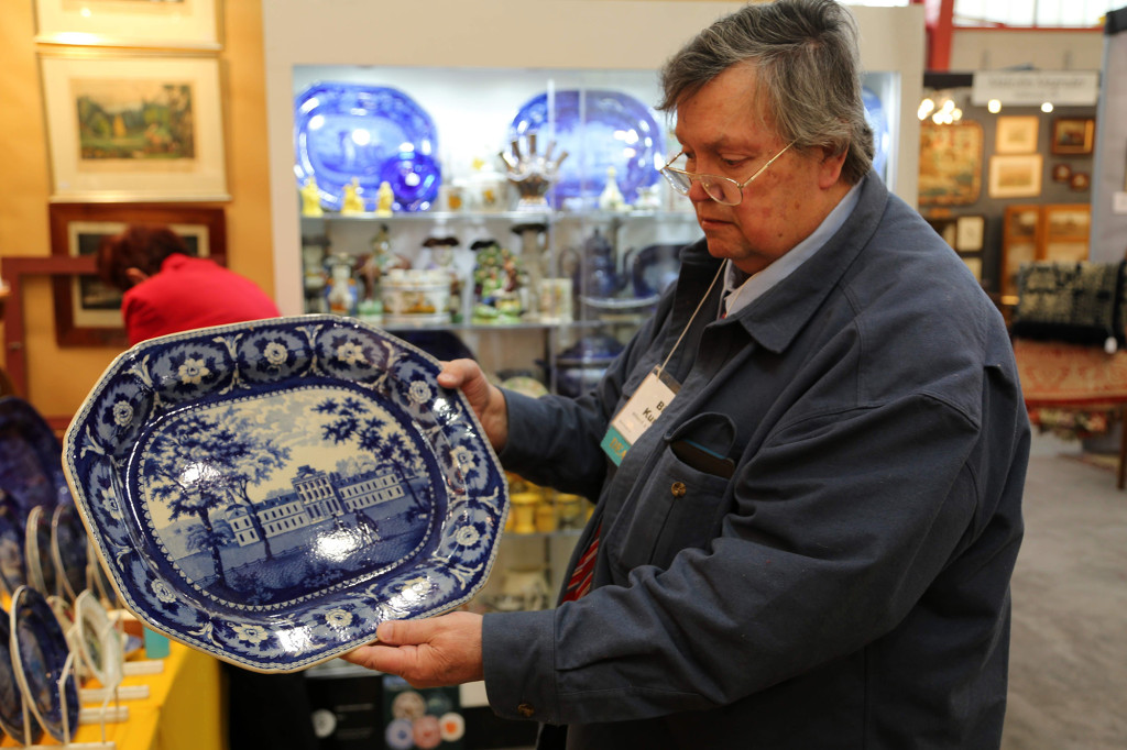 """At the 2019 Chester County Antiques Show, Bill Kurau held up a Staffordshire Pennsylvania Hospital platter by John & William Ridgway, made as part of the firm's """"Beauties of America"""" series."""