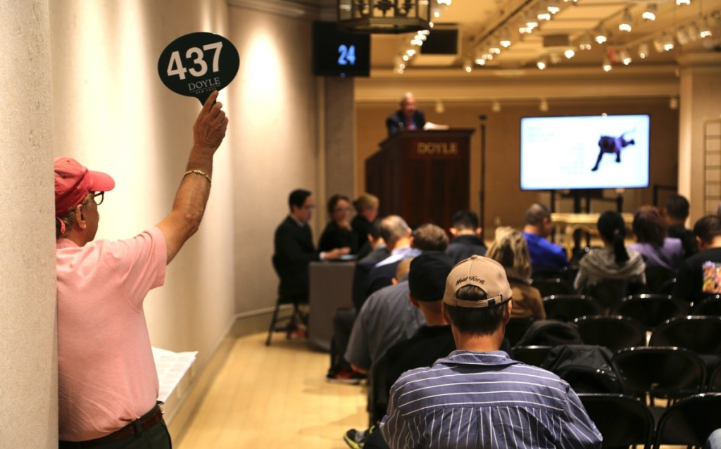 A bidder at the back corner of the room holds his paddle high in the Fall 2019 Asia Week New York.   —Doyle