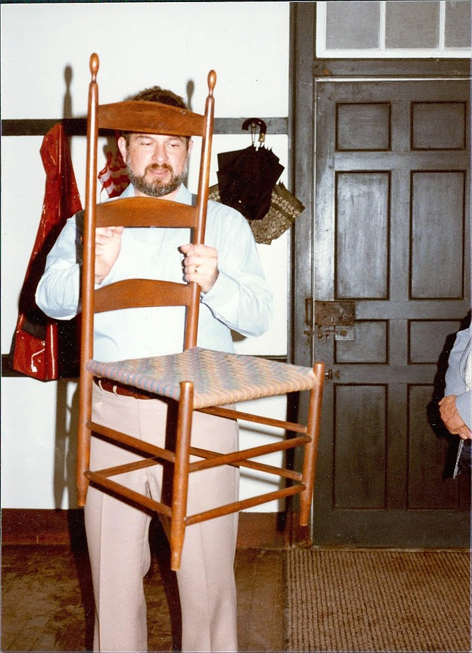 A younger Chuck Muller holds up a Shaker chair at a lecture.