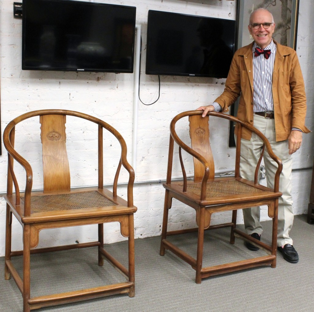 Asian specialist and auction house owner Lark Mason stands with a pair of rare Chinese huanghuali continuous horseshoe back armchairs dating from the early Qing dynasty that were expected to bring up to $900,000 in sales that run through November 5.
