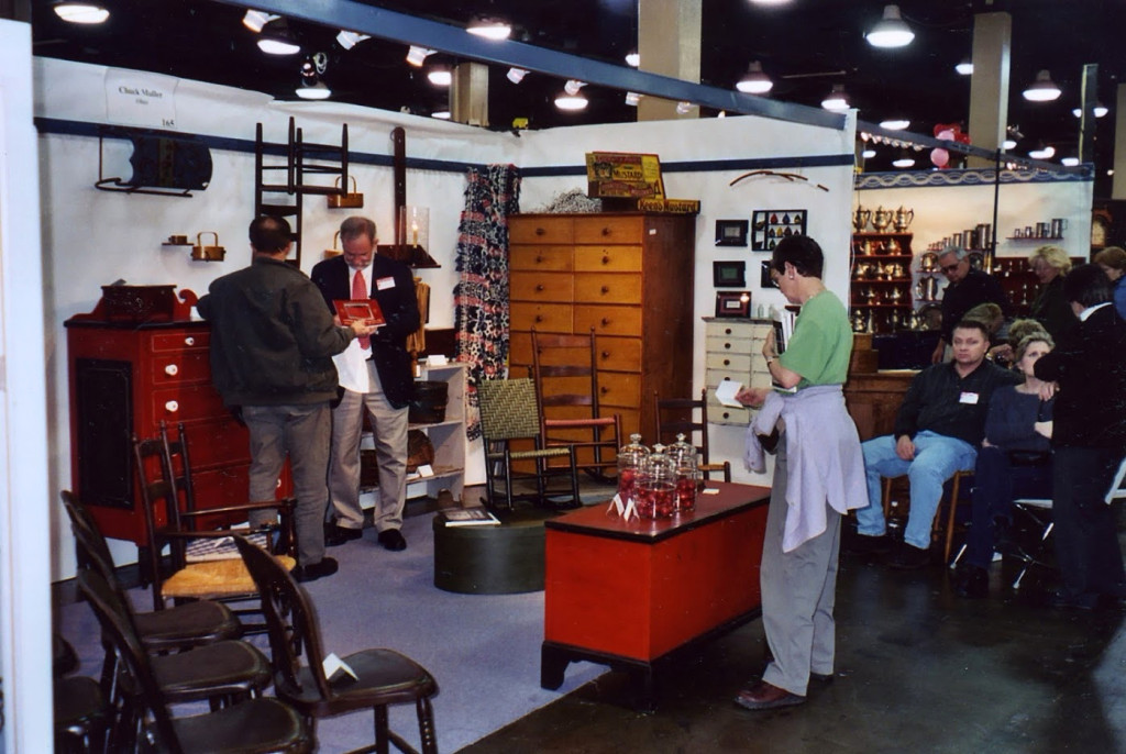 Chuck appears ready to give a lecture in his booth as visitors arrange chairs outside at an unidentified show. The booth is full of Shaker and Soap Hollow examples.