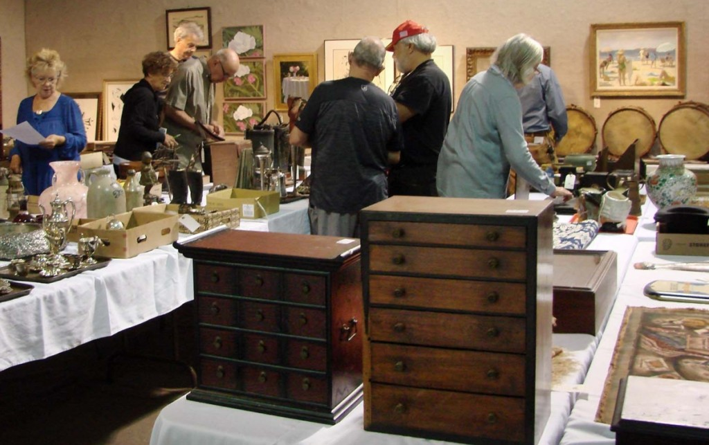 Several prospective buyers examine the merchandise prior to the start of the sale.