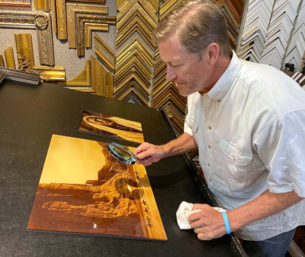 "Paul Unks examines a gold tone of Curtis' ""Canyon de Chelly,"" before framing."