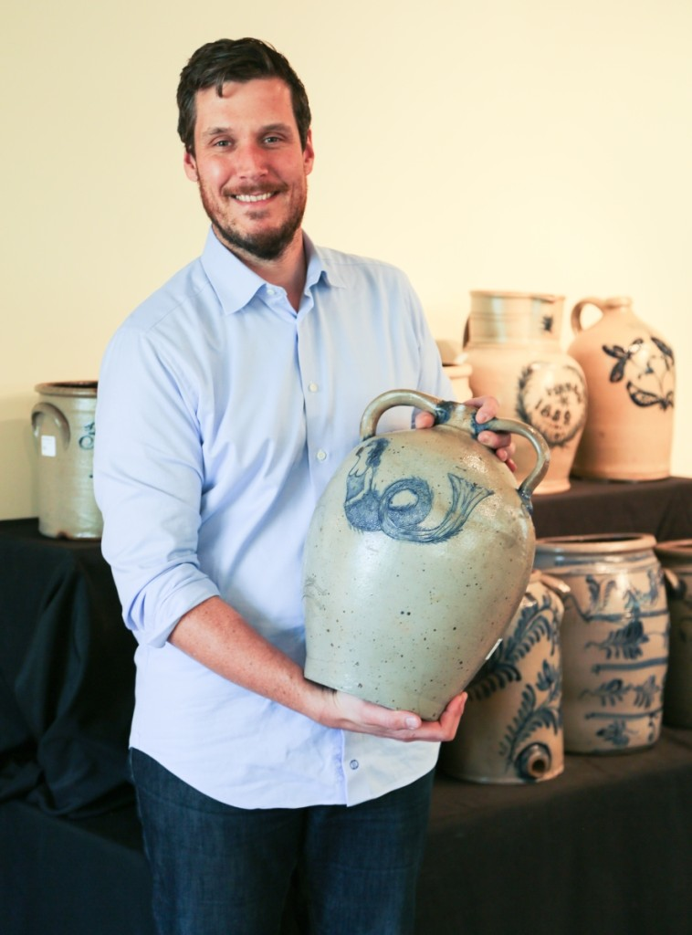 Luke Zipp, specialist and auctioneer, stands with the sale's top lot in a stoneware presentation cooler with incised mermaid and seahorse motifs by Cornwall, N.Y., potter Moses Clark Bell. The cooler brought $70,800, selling to dealer Jim Kilvington in the gallery who was bidding on behalf of a client. It was only the third mermaid-decorated piece the firm had ever seen.