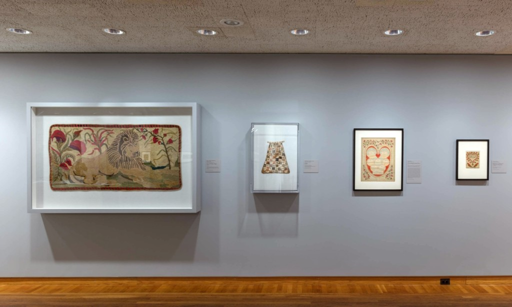 On the wall at left, a hooked rug depicting a recumbent lion after a design by Ebenezer Ross, active 1890-1900. At center right, an 1811 genealogical drawing in ink and watercolor by Lydia Smith.
