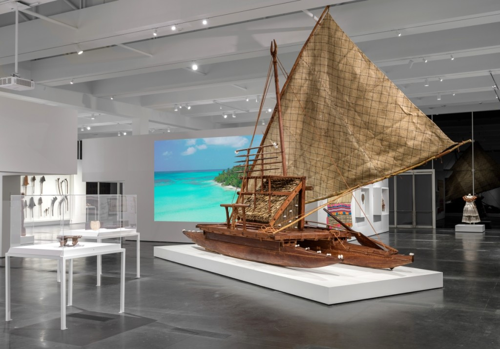 This contemporary drua (double-hulled sailing canoe) was commissioned as a heritage project in Fiji to encourage the retention of canoe-building skills. Joji Marau Misaele managed the project in Fiji with the drua building team — carvers and mat-sail-makers — originally from the islands of Ogea and Vulaga in the Lau region. The team harvested trees from the forests on Ogea and completed the canoe, which has no metal components, using traditional tools, fiber lashings, and shells. The sail is composed of six sections of hand-woven pandanus-leaf matting, which prevents tearing of the entire sail. Without a fixed bow or stern, drua can sail in either direction. In the Nineteenth Century, large double-hulled canoes provided effective open ocean transportation and carried troops in times of war. Installation photograph, Los Angeles County Museum of Art. Photo ©Museum Associates/LACMA.