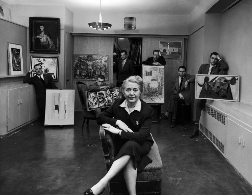 Edith Halpert at the Downtown Gallery, in a photograph for Life magazine in 1952. She is joined by some of the new American artists she was promoting that year: Charles Oscar, Robert Knipschild, Jonah Kinigstein, Wallace Reiss, Carroll Cloar and Herbert Katzman. Photograph ©Estate of Louis Faurer.