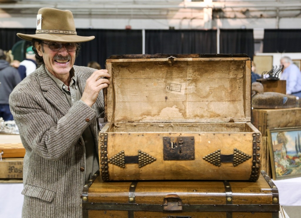 Paul Norton of Hartco Trunks, Terryville, Conn., stands next to a log trunk from 1819.