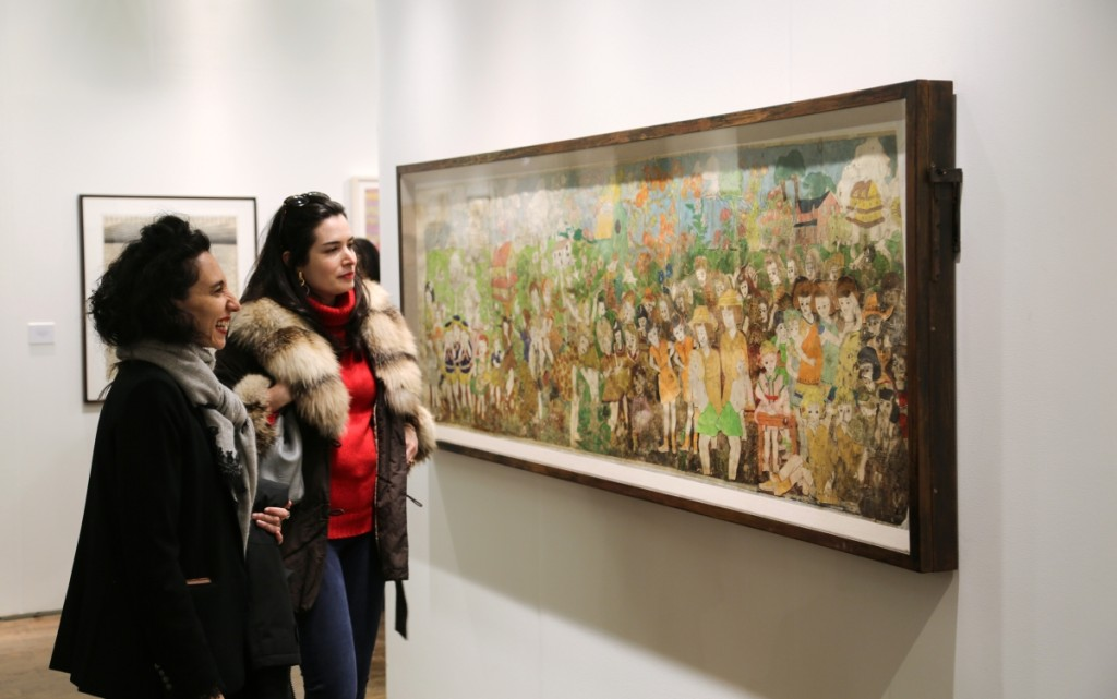 Two women admire the Henry Darger work that sold at Andrew Edlin Gallery, New York City.