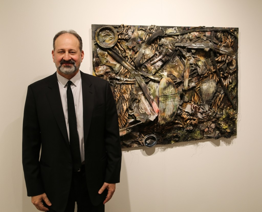 "Fair owner Andrew Edlin stands next to ""Working at Home,"" a circa 2000 work by Thornton Dial that had just sold. Andrew Edlin Gallery, New York City."