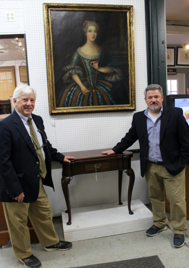 """Copake co-owners Mike Fallon, left, and Seth Fallon with one of the sale's key lots, a rare Eighteenth Century Queen Anne turret top card table. There were close to ten competitive bids on the piece. """"We're happy that it went to a Midwest collector on the phone,"""" said Mike."""