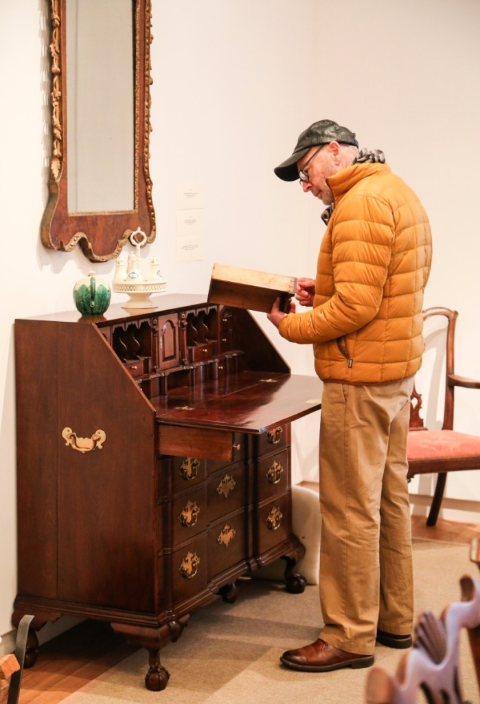 A previewer takes a good look at the Chippendale block front desk from Salem, Mass., which went out at $28,125.