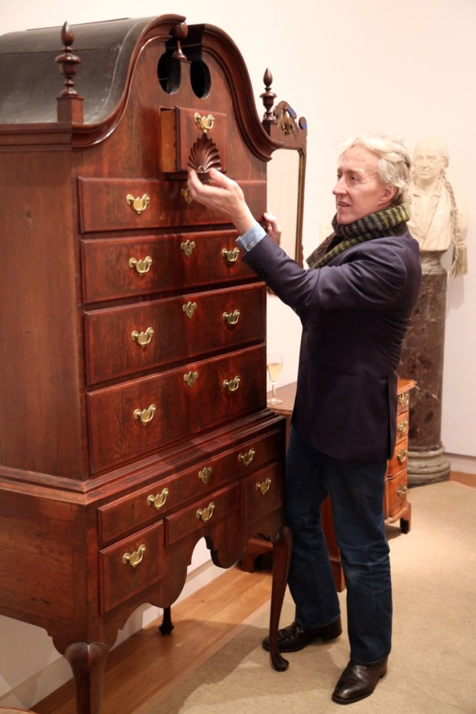 Auctioneer Leigh Keno examines the deep fan carving on the Samuel Gardner Salem, Mass., Queen Anne bonnet-top high chest of drawers. It went on to sell for $56,250.