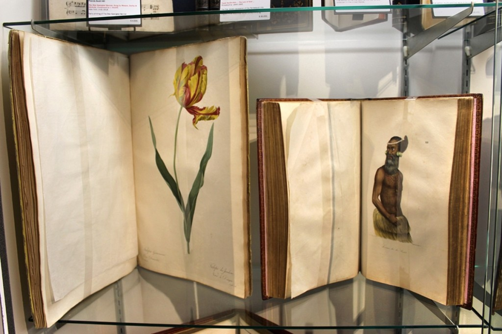 """Two rare tomes on offer at Donald Heald Rare Books, New York City — left, the 1824 album of botanicals by Pierre Joseph Redoute and a fundamental hand-colored work by Louis Choris on Alaska, California and Hawaii, characterized as """"one of the most beautiful books of travel in existence."""""""