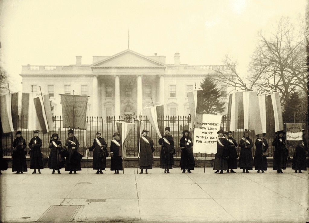 The Silent Sentinels were the first group to demonstrate at this strategic location. Women Suffrage Pickets at the White House, 1917.   Harris & Ewing Photograph Collection, Library of Congress.