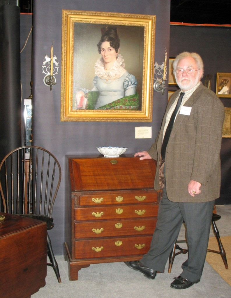 Lee Hanes stands in his booth, surrounded by American furniture, fine art and metalware.