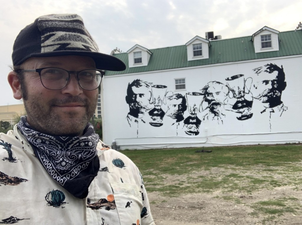 Artist Zach DePolo stands in front of the George Ohr mural.