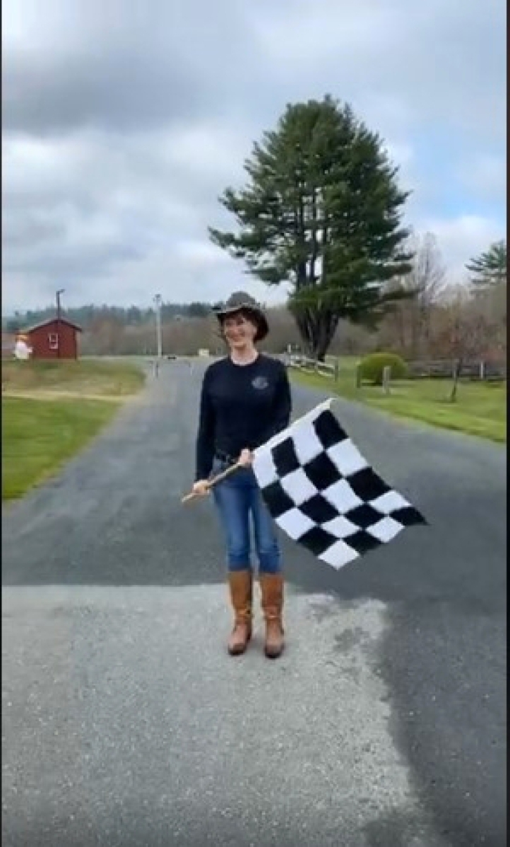 Kate Corriveau waving her checkered flag to virtually open Brimfield Auction Acres, filmed live by Crisafulli on Friday morning, May 15.                —Facebook, Brimfield Live