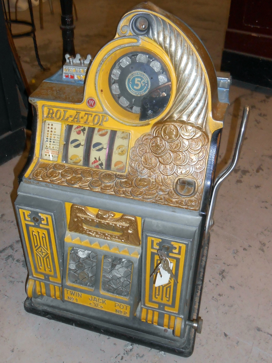 """Rolling to the top of the sale was this Rol-A-Top 5-cent slot machine by Watling that a private collector bought for $5,750. It retained its original paint and finish with wear but what was a particularly nice feature, according to Opfer, was the dispenser on the front of it that he described as """"mint."""" ($ ,000)."""