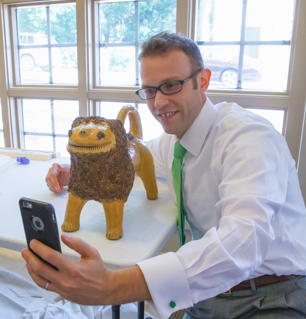 Daniel Ackermann taking a selfie with MESDA's iconic Solomon Bell lion   during the installation of the William C. and Susan S. Mariner   Southern Ceramics Gallery in 2015. —Robert Hunter photo.